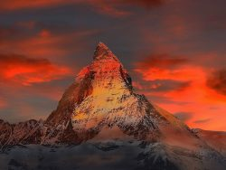 A sharply pointed mountain appears red and yellow in a deeply coloured sunset (switzerland)