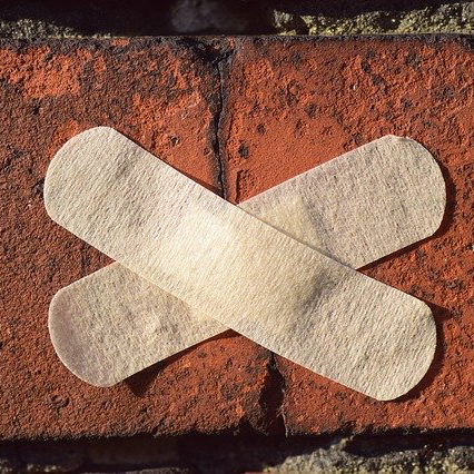 Two plasters stuck in a cross over a crack in a brick wall