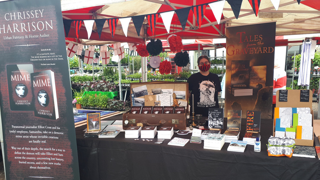 Chrissey's stall at the Newark Book Festival Literature Village. Black, white and red bunting, roller banners, copies of Mime in a vintage suitcase surrounded by occult items.