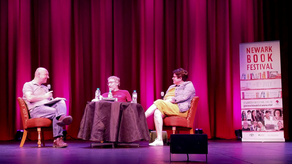 Panel at Newark Book festival. The moderator and two authors sit around a table on a stage with a purple curtain behind.