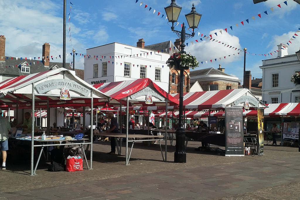 Newark-on-Trent market square. Red and white canopies of market stalls, bunting strung from a Victorian style lamp post. Blue sky.